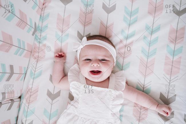 Cheerful baby girl lying in crib at home