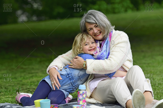 Affectionate grandmother and granddaughter embracing while sitting in public park