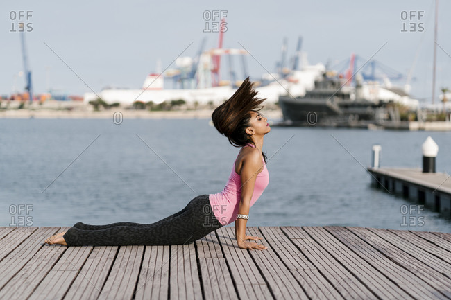 Female athlete with eyes closed practicing cobra pose on pier against sea at harbor