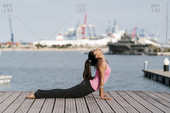 Woman practicing cobra pose on pier against sea at harbor