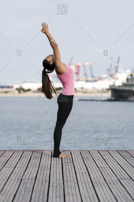 Female athlete practicing upward tree position while standing on pier against sea