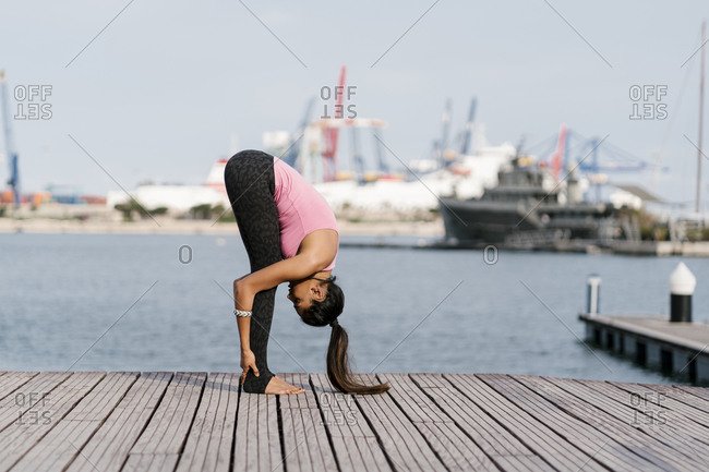 Female athlete practicing standing forward bend pose on pier against sea at harbor