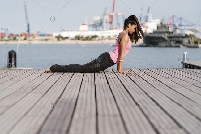Female athlete practicing cobra pose on pier at harbor
