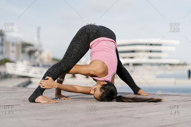 Female athlete practicing wide-legged forward bend on pier against sky