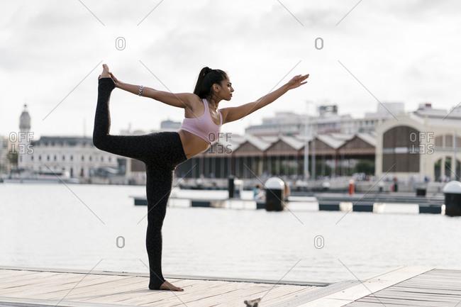 Female athlete practicing Natarajasana on pier against sky in city