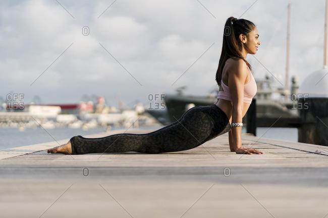 Athlete practicing upward facing dog pose on pier at harbor