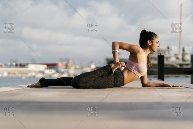 Female athlete practicing half frog pose on pier at harbor