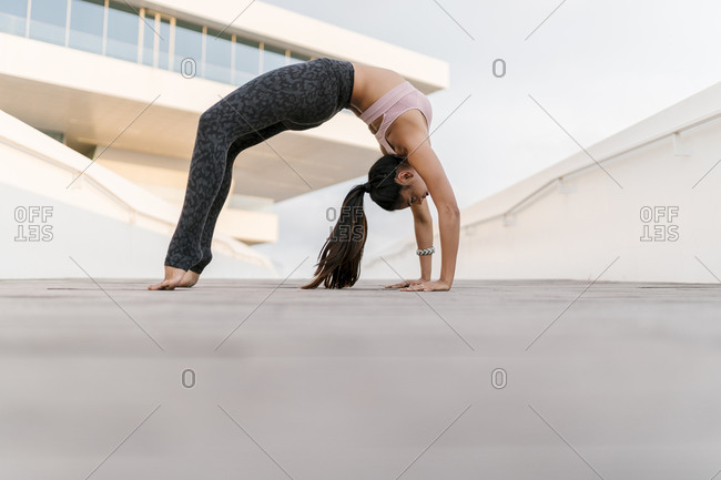 Female athlete practicing wheel pose against building in city