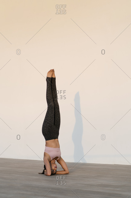 Female athlete practicing headstand on hardwood floor against wall
