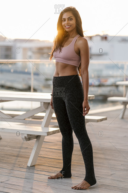 Smiling female athlete standing on pier against clear sky during sunset