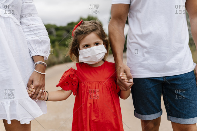 Girl wearing mask while holding hands of parents on country road