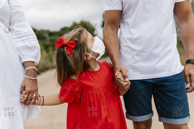 Girl wearing mask looking at father while holding hands on country road