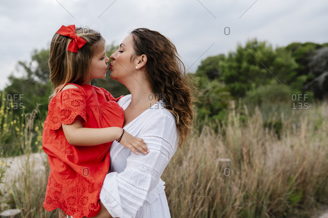 Affectionate mother and daughter kissing at countryside
