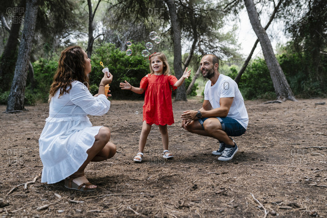 Woman blowing bubbles for daughter with father in forest