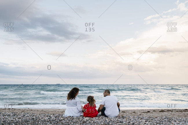 Family spending quality time on shore at beach against cloudy sky