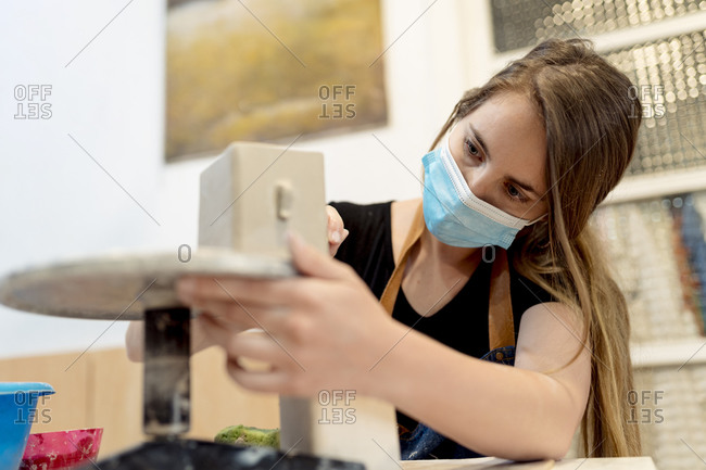 Close-up of young woman wearing mask making pottery in studio
