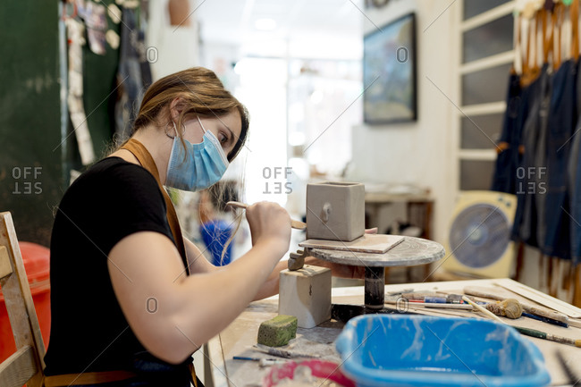 Young woman wearing mask making ceramic on workbench in workshop
