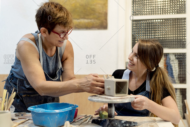 Mature woman teaching pottery to coworker in workshop