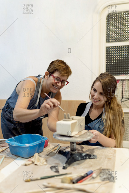 Mature woman teaching pottery to female coworker in workshop