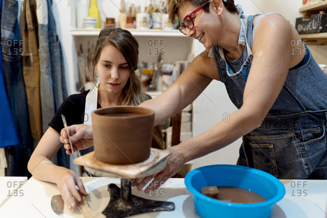 Mature woman teaching pottery to female coworker in studio