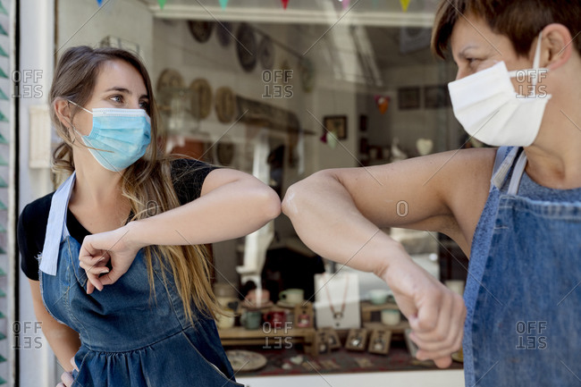 Close-up of female coworkers wearing masks giving elbow bump while standing outdoors