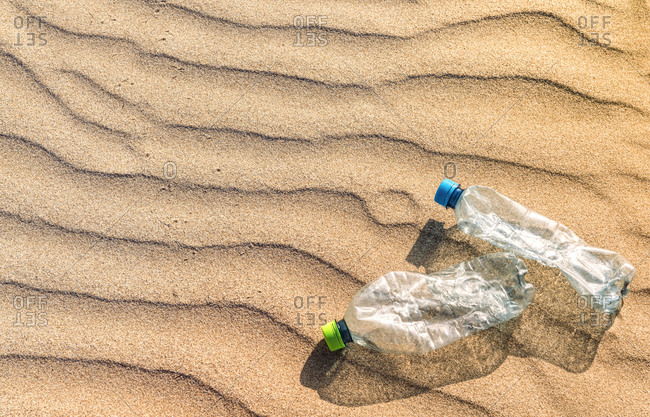 Plastic bottles lying on rippled beach sand