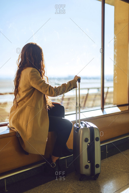 Businesswoman holding wheeled luggage while sitting on window sill at airport departure area