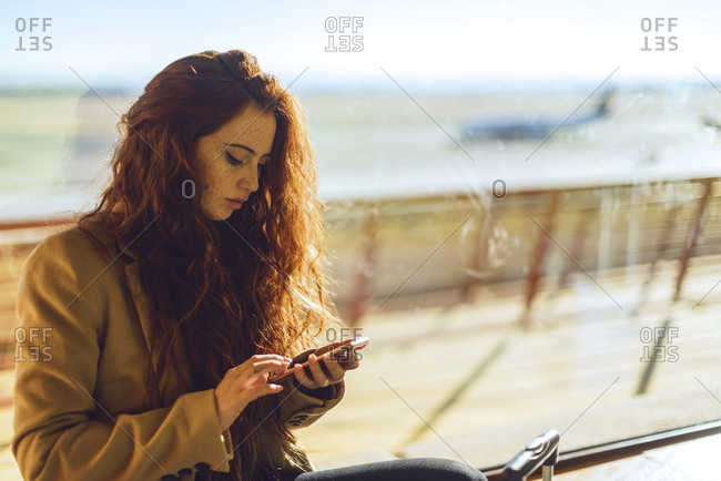 Businesswoman using smart phone by window at airport departure area