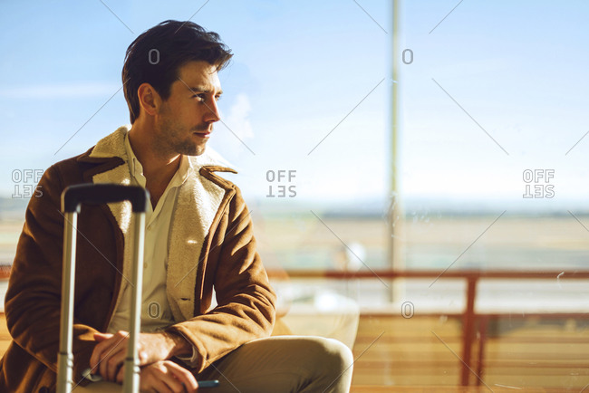Thoughtful businessman sitting on window sill at airport departure area