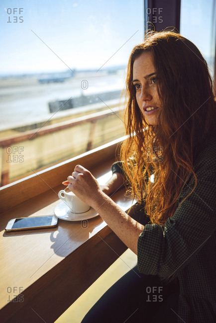 Thoughtful businesswoman stirring coffee at airport cafe