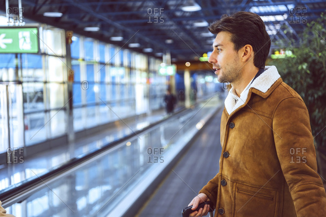 Thoughtful businessman standing on moving walkway at airport