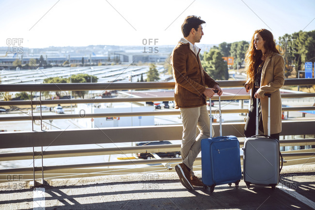 Business couple talking while standing on elevated walkway at airport