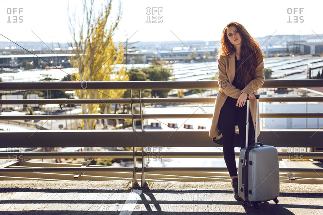 Confident businesswoman holding luggage on elevated walkway at airport during sunny day