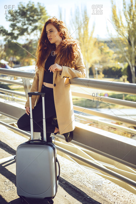 Thoughtful businesswoman standing with luggage on elevated walkway at airport during sunny day