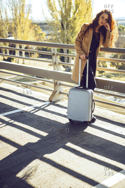 Confident businesswoman standing with luggage on elevated walkway at airport during sunny day