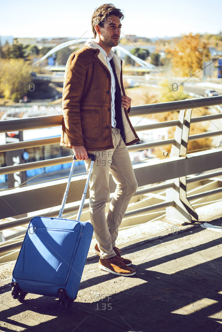 Thoughtful businessman holding luggage while standing on elevated walkway at airport during sunny day