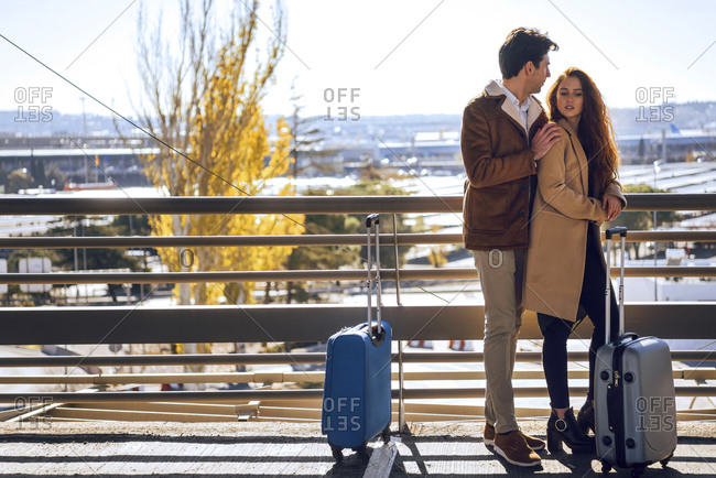 Romantic business couple standing on elevated walkway at airport