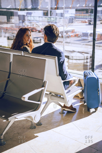 Business couple talking while waiting at airport departure area