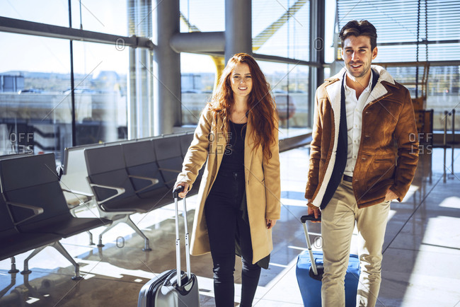 Confident business couple standing with luggage at airport departure area