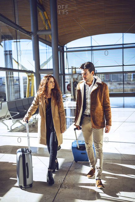Business couple talking while walking with luggage at airport departure area