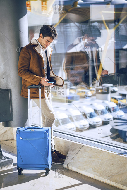 Businessman using smart phone by window at airport departure area