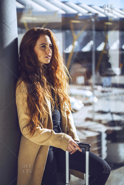 Thoughtful businesswoman standing with luggage by window at airport departure area