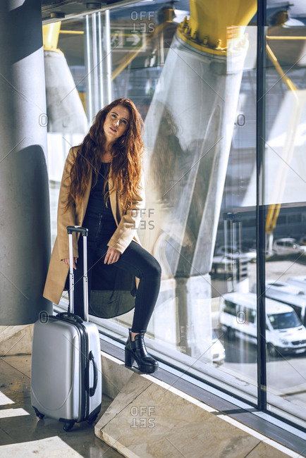 Confident businesswoman standing with luggage by window at airport departure area