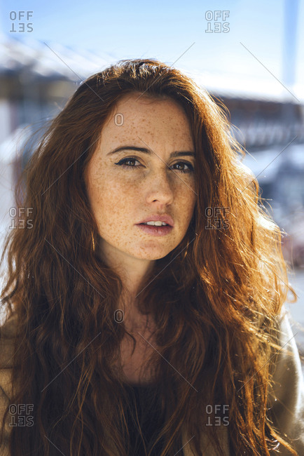 Confident woman with freckles on face during sunny day