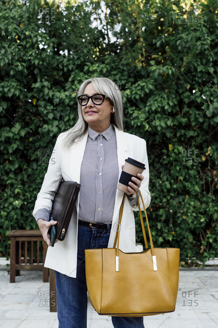 Senior businesswoman holding disposable cup and document with purse at garden