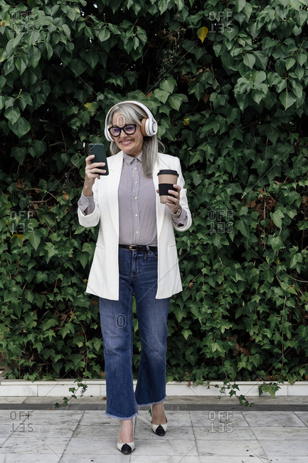 Smiling female professional listening music while enjoying coffee against plants in garden during break
