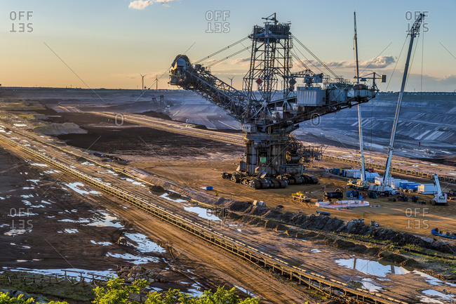 High angle view of bucket-wheel excavator at mine against sky during sunset