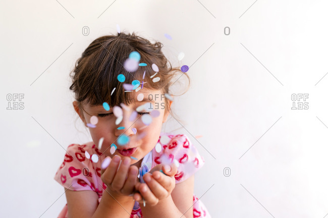Close-up of cute girl blowing confetti from hands against white background