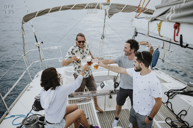 Friends toasting beer while enjoying on sailboat in sea
