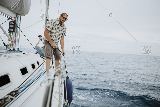Sailors removing bumpers on sailboat in sea against sky